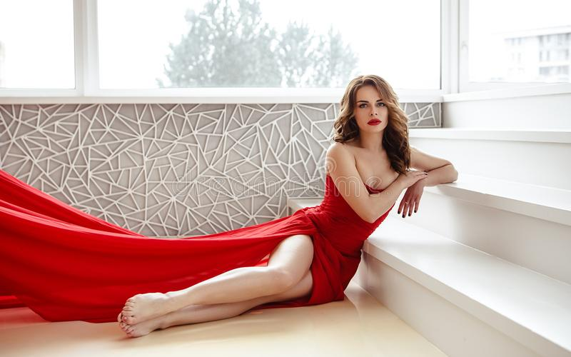 Beautiful brunette woman in a red dress, fashion beauty portrait stock photo
