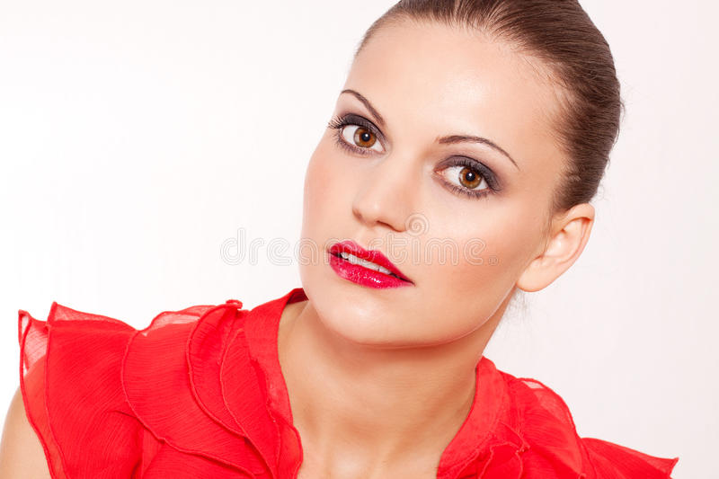 Beautiful brunette woman with red lips and makeup. Beautiful brunette woman with red lips and red shirt royalty free stock photography