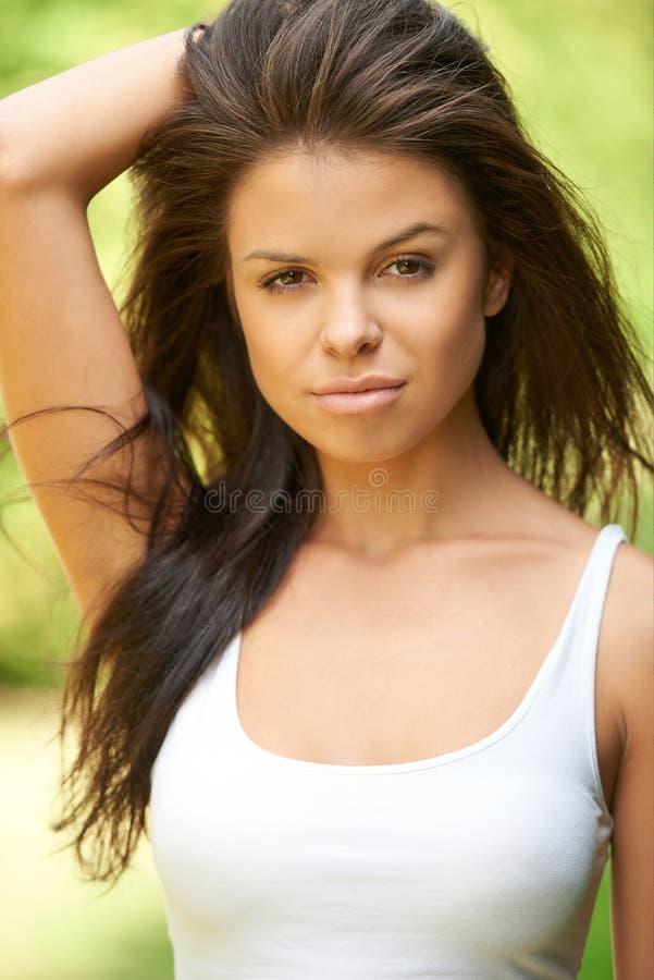 Beautiful brunette woman relaxing at green surroundings