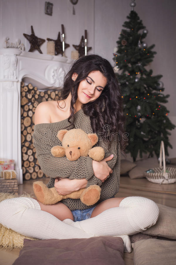 Beautiful brunette woman in shorts and sweater in new year decor royalty free stock photography