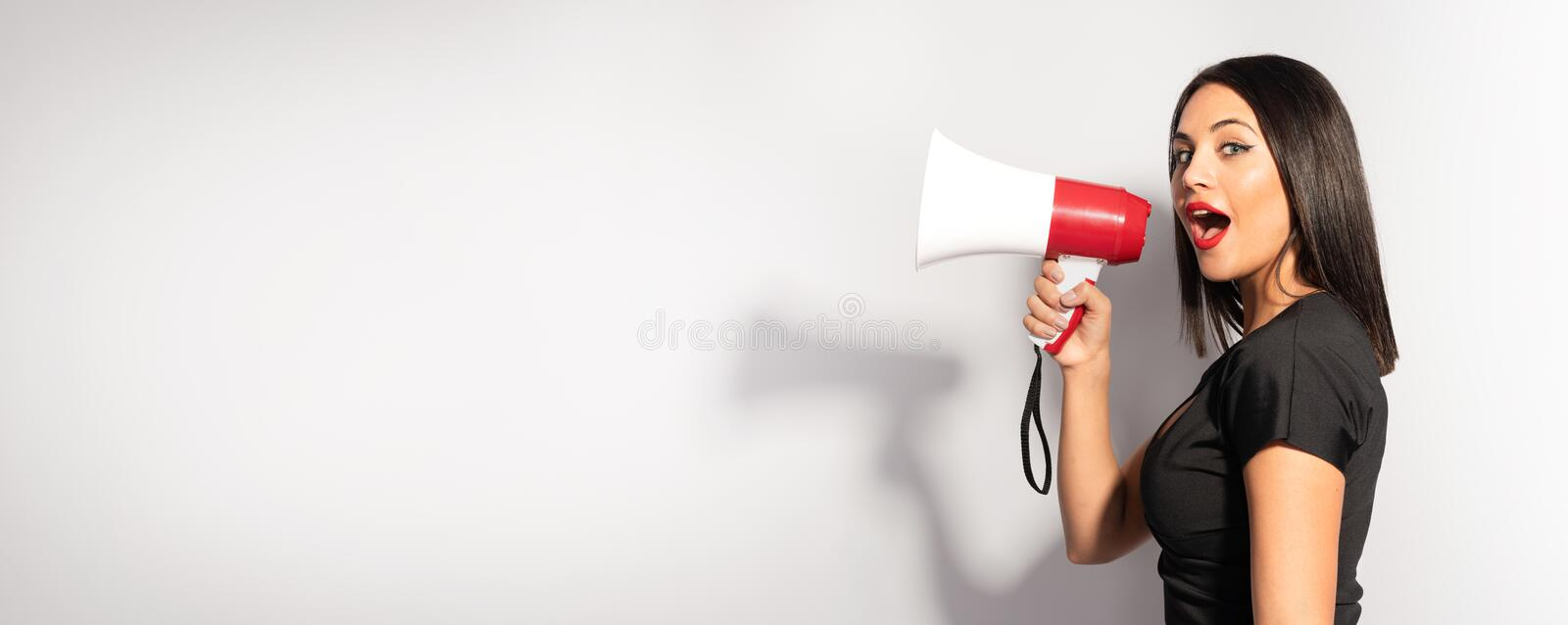 Beautiful Brunette Woman Shouting Through the Megaphone. Advertising Concept. Beautiful Brunette Woman Shouting Through the Megaphone. Communication and stock photography