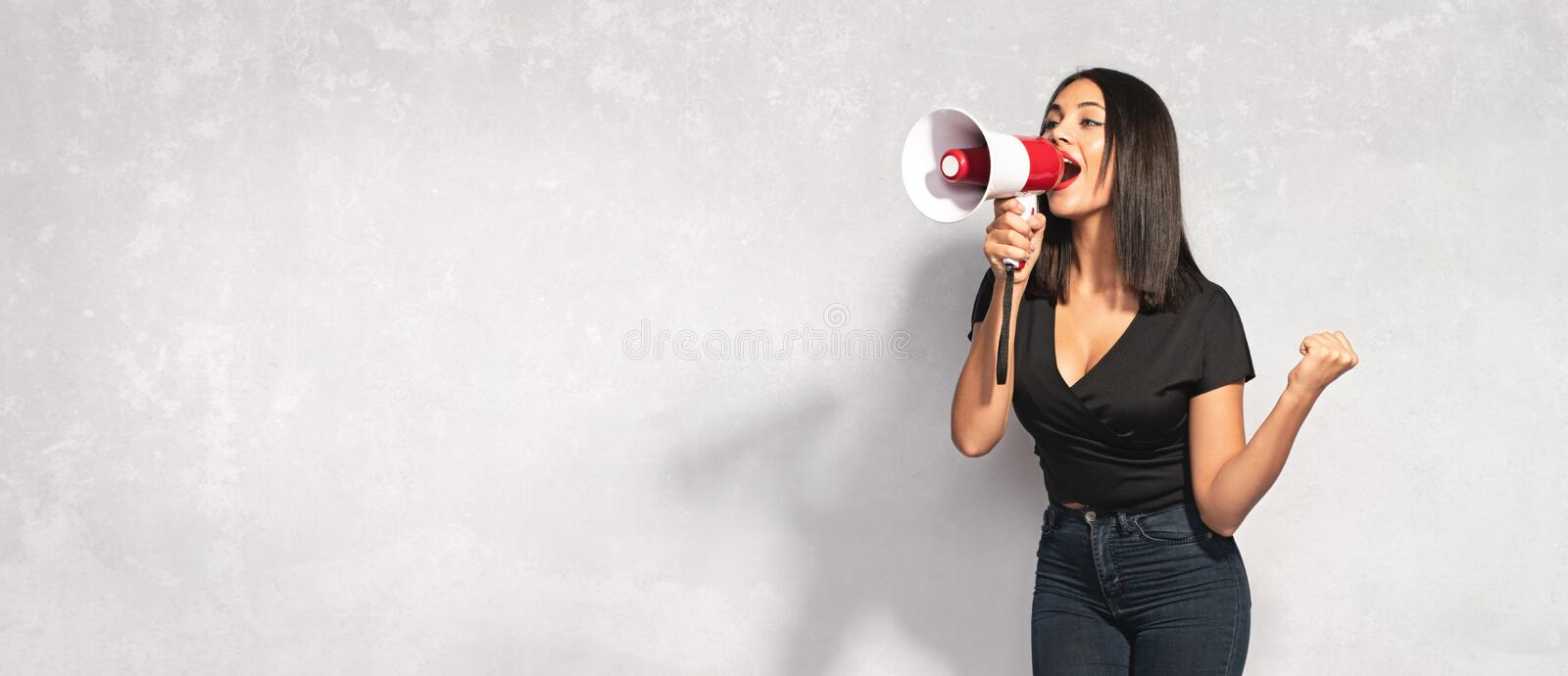 Beautiful Brunette Woman Shouting Through the Megaphone. Advertising Concept. Beautiful Brunette Woman Shouting Through the Megaphone. Communication and stock image