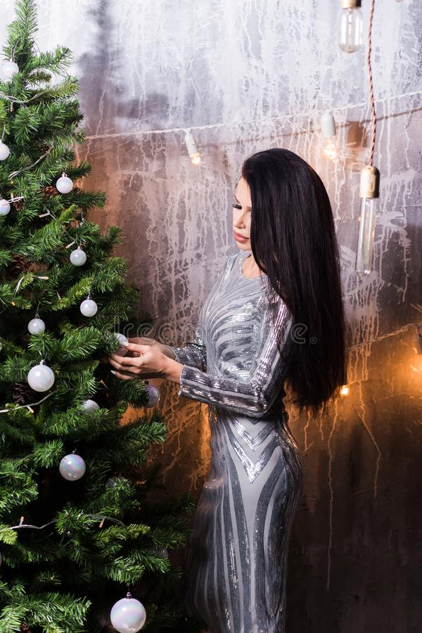 Beautiful brunette woman in silver dress decorating Christmas tree with baubles. New Year, holiday, celebration, winter concepts stock photos