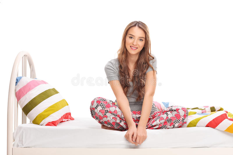 Beautiful brunette woman sitting on a bed stock image
