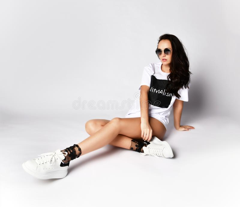 Beautiful brunette woman sitting on grey background in long white t-shirt and sneakers. Happy laughing smiling in sunglasses on white background royalty free stock photography