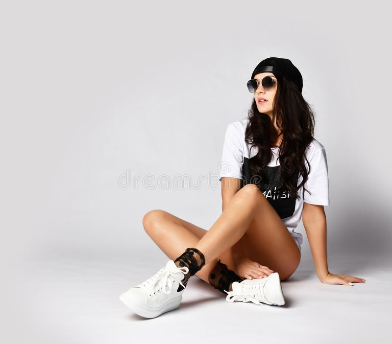 Beautiful brunette woman sitting on grey background in long white t-shirt and sneakers. Happy laughing smiling in sunglasses on white background stock photos