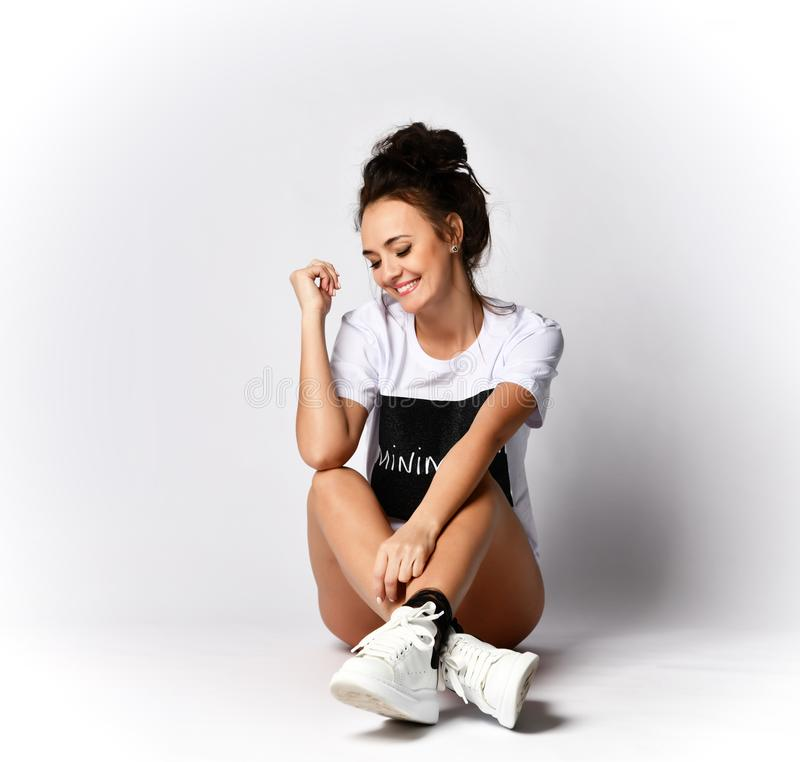 Beautiful brunette woman sitting on grey background in long white t-shirt and sneakers. Happy laughing smiling stock images