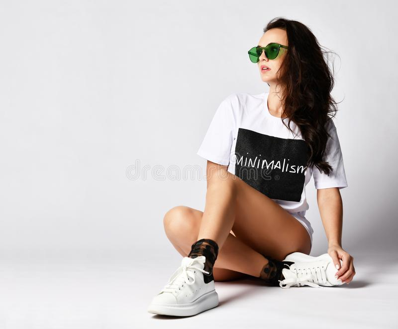 Beautiful brunette woman sitting on grey background in long white t-shirt and green sunglasses. Beautiful brunette woman sitting on grey background in long white royalty free stock images