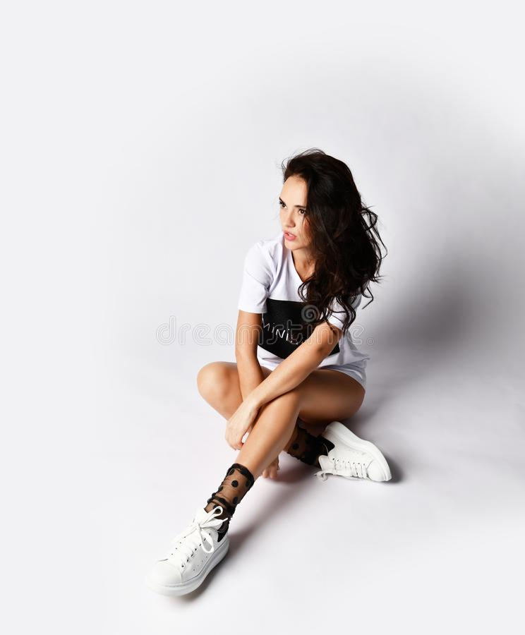 Beautiful brunette woman sitting on grey background in long white t-shirt and sneakers. Happy laughing smiling in sunglasses on white background stock images