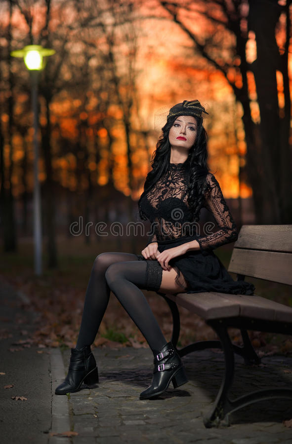 Beautiful brunette woman sitting outside in park with dramatic sky on background. Fashionable female with cap resting on bench royalty free stock photography