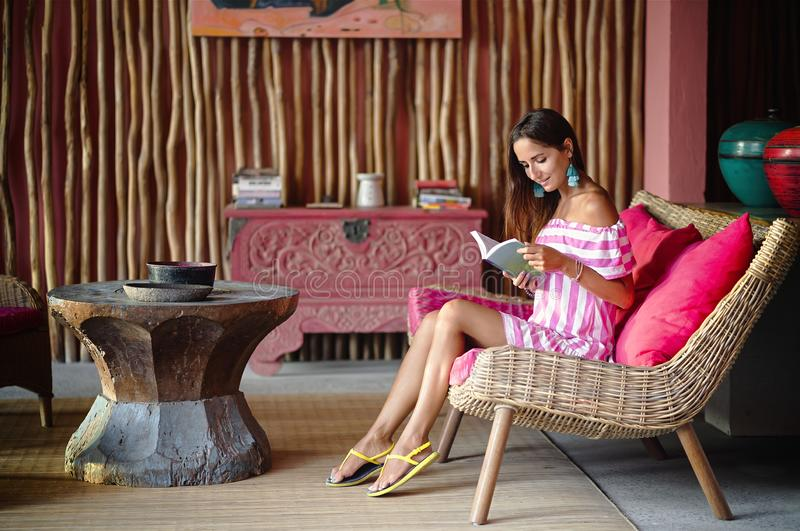 Beautiful brunette woman sitting on a pink couch and reading a book and smiling. Interior in ethnic style stock photos