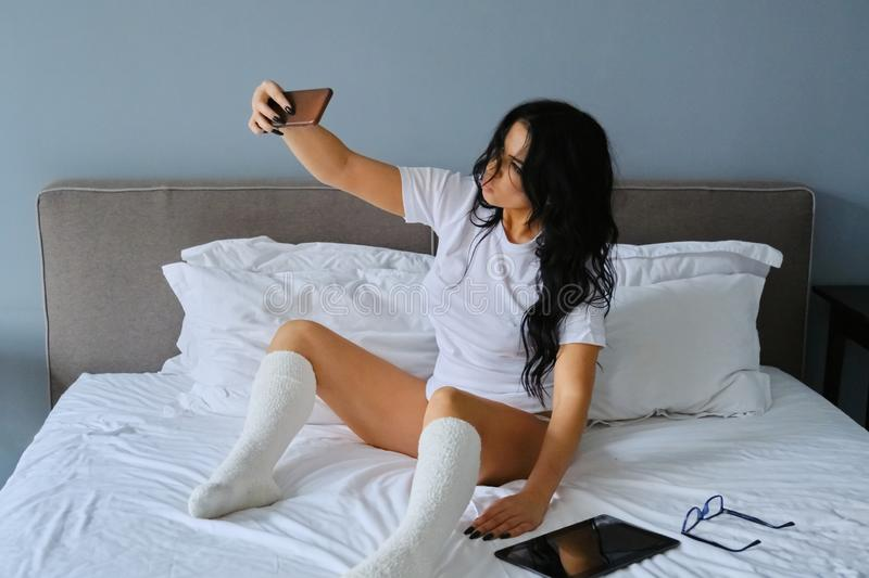 Beautiful brunette woman sitting in white bed taking selfie royalty free stock photography