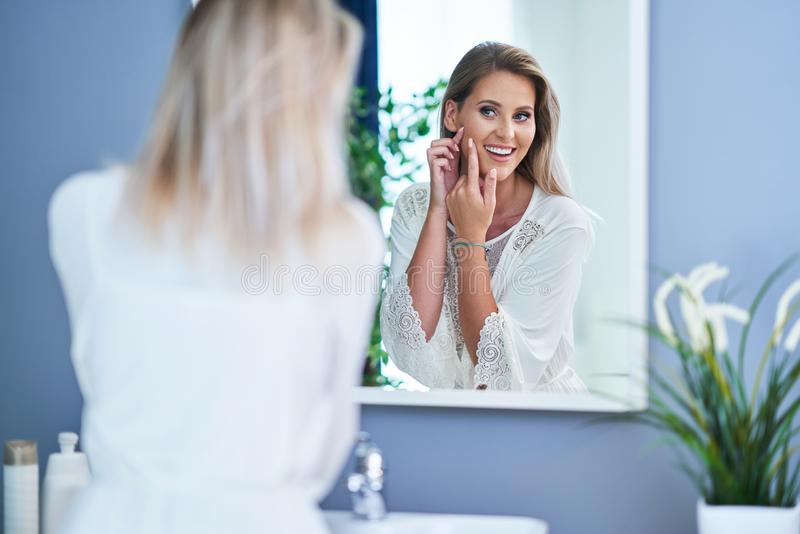 Beautiful brunette woman with skin problems in the bathroom. Picture of adult brunette woman in the bathroom royalty free stock images