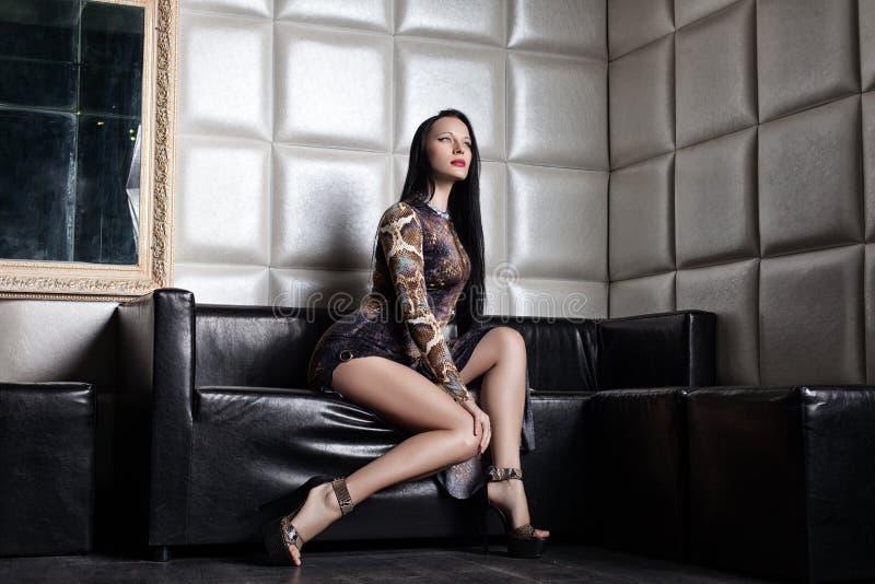 Beautiful brunette woman on sofa in nightclub stock image