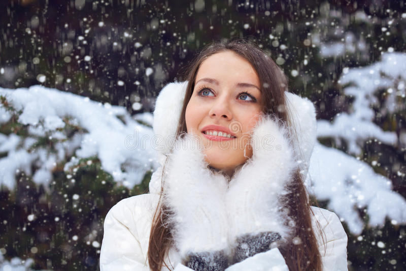 Beautiful brunette woman standing under snowfall royalty free stock photo