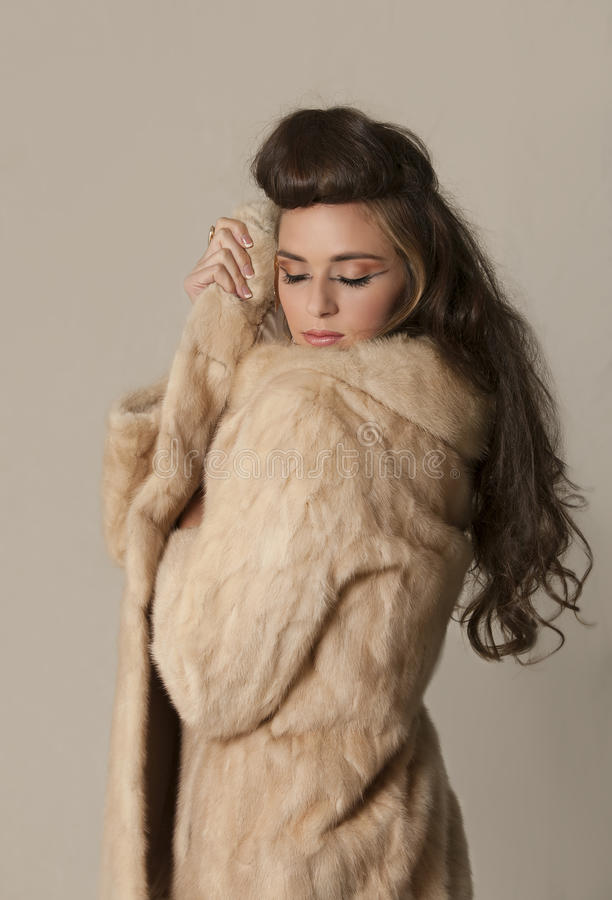 Beautiful brunette woman with tribal makeup and fur coat stock photography