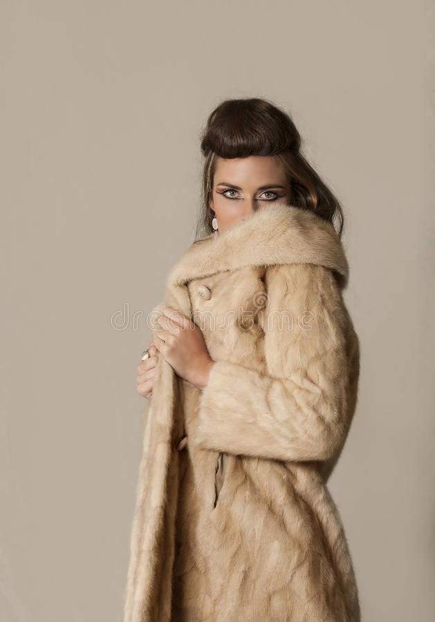 Beautiful brunette woman with tribal makeup and fur coat royalty free stock photos