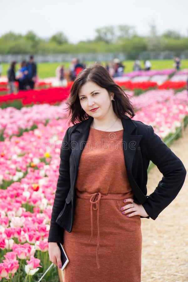Beautiful brunette woman with tulips in field of flowers royalty free stock photo
