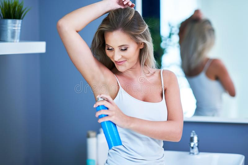 Beautiful brunette woman using deodorant in the bathroom. Picture of adult brunette woman in the bathroom stock photography