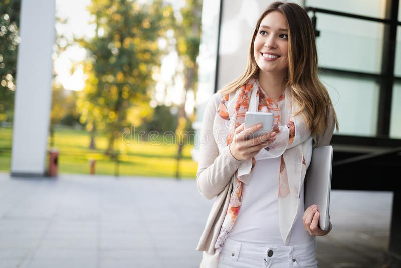 Beautiful brunette girl using smart phone for work, freelance, blogging, studying, shopping. Beautiful brunette woman using mobile for work, freelance, blogging stock photography