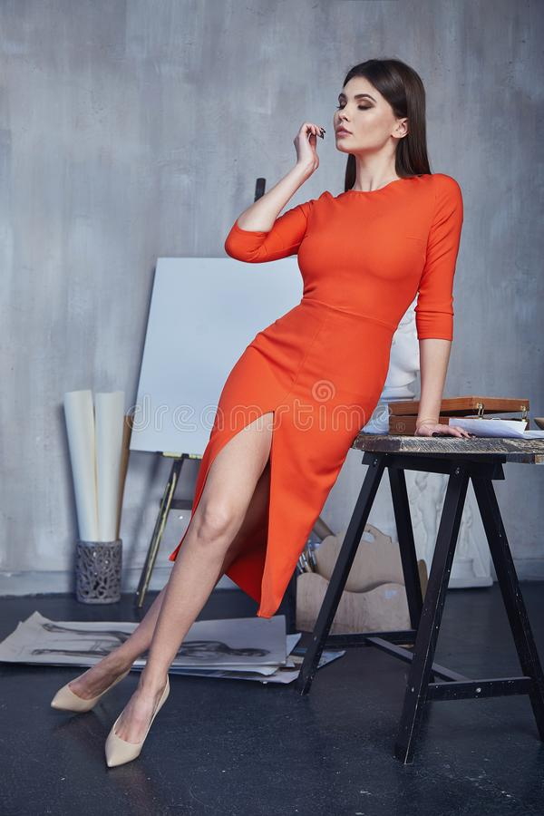 Beautiful brunette woman wear casual fashion style clothes pretty face orange long dress accessory shoes in interior art, workshop royalty free stock image
