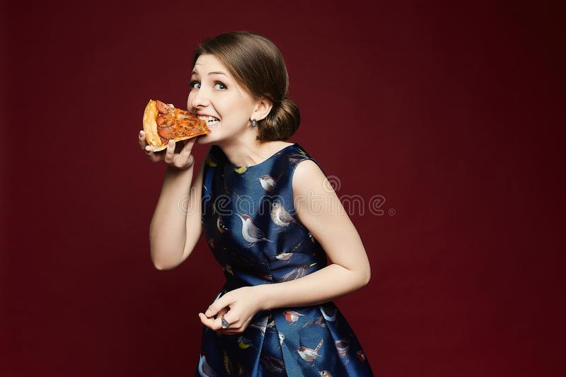Beautiful brunette young woman with blue eyes in a fashionable blue dress holding a piece of pizza in her hand and. Eating it, isolated at red background stock photo