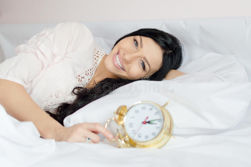 Beautiful brunette young woman blue eyes girl waking up lying in bed holding alarm clock happy smiling & looking at camera. Cheerful brunette female waking up royalty free stock photos