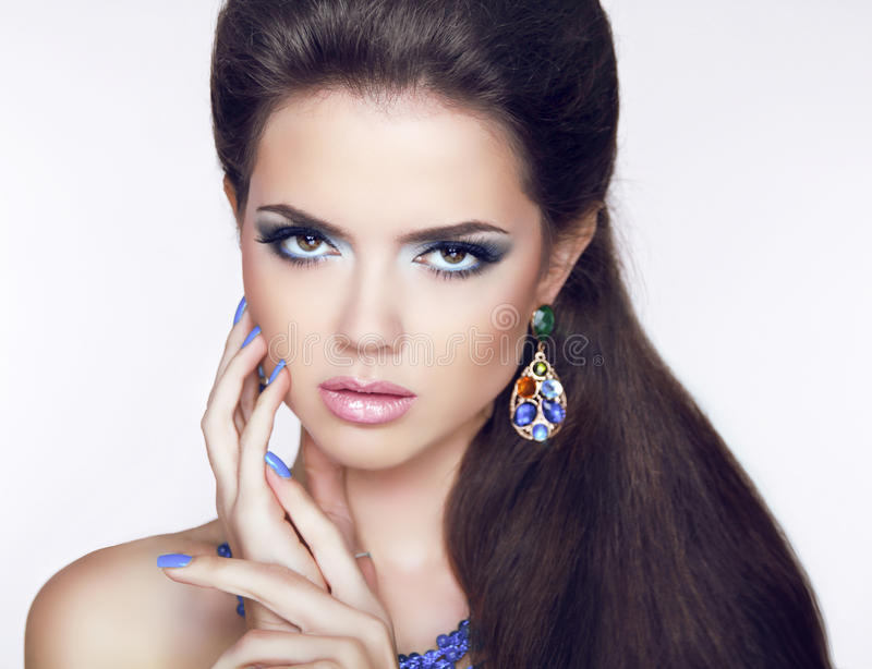 Beautiful Brunette young woman with fashion earring. Makeup. Man stock image