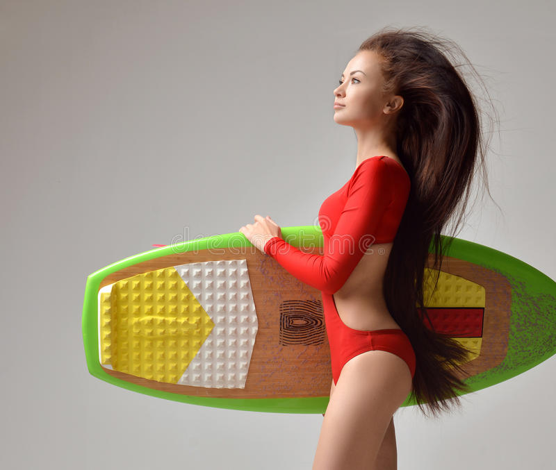 Beautiful brunette young woman with long hair and surfboard stock photography