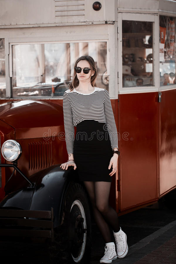 Beautiful brunette young woman wearing dress, black circle glasses and walking on the street, posing near retro vintage car. Flare stock photos