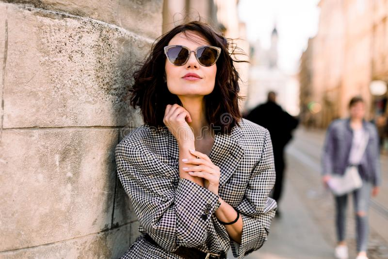 Beautiful brunette young woman wearing jacket and black sunglasses walking on the street, posing near the old building royalty free stock image