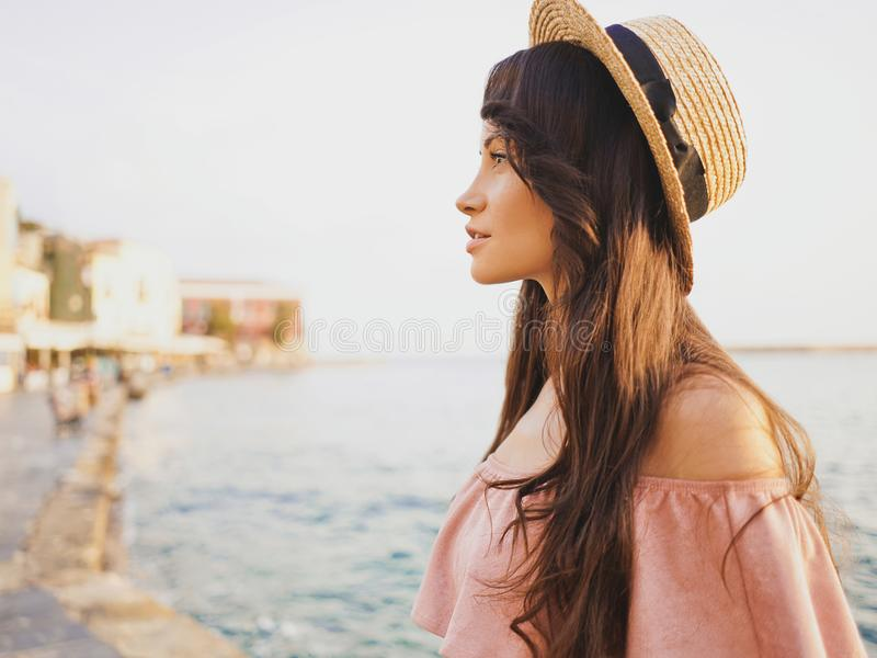 Stylish brunette woman enjoying sunrise on seafront stock photography