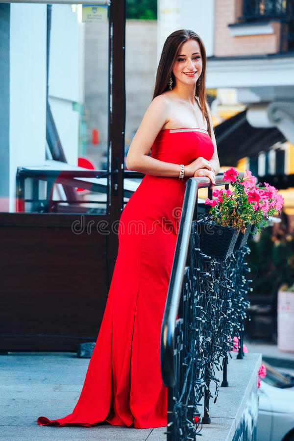 Beautiful brunette young woman wearing red dress,walking on the street.Fashion photo royalty free stock images