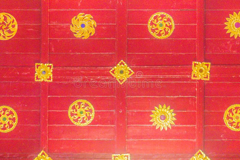Beautiful Buddhist church interior with wooden red ceiling background and golden patterned decoration. stock images