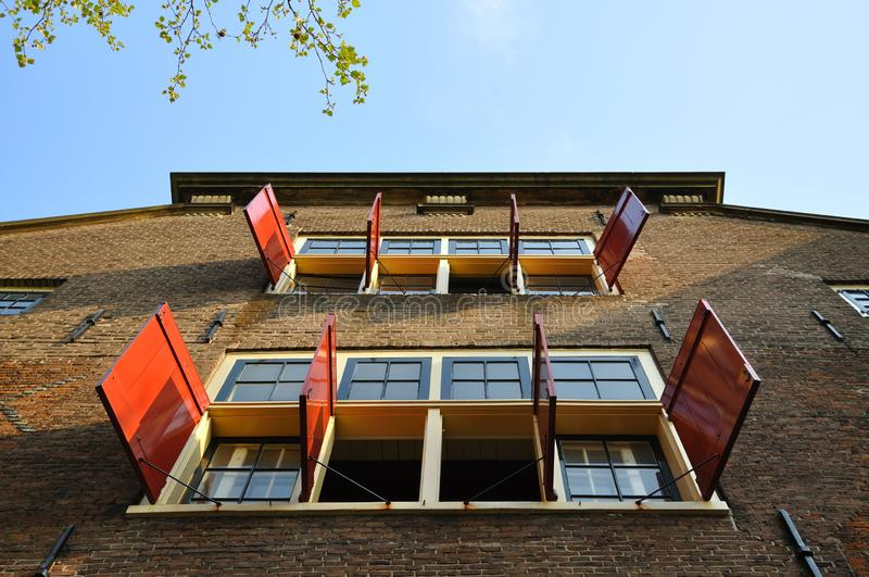 Beautiful building with open sun blinds and windows in Amsterdam, Holland Netherlands.  stock photos