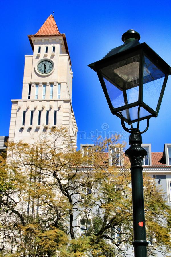 Building with a tower with clock in Lisbon. Beautiful building with a tower with clock in Dom Luis I square in Lisbon. Vintage Lamp post in the foreground royalty free stock image