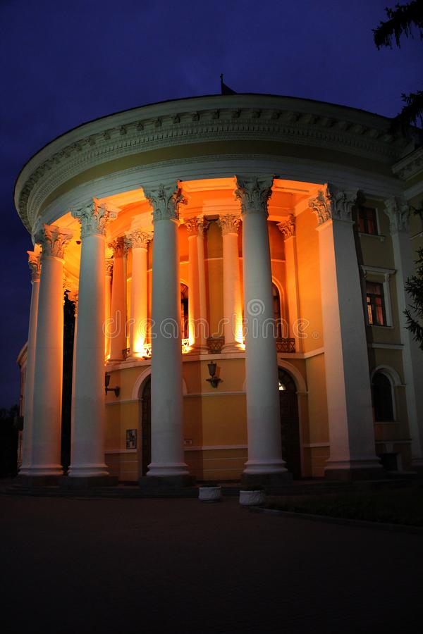 Beautiful building with white columns illuminated by lights at nighttime. Architectural ensemble illuminated at night. Classic architecture in construction stock photos