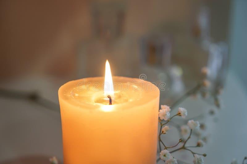 Beautiful burning candle with flowers on shelf, closeup stock photography