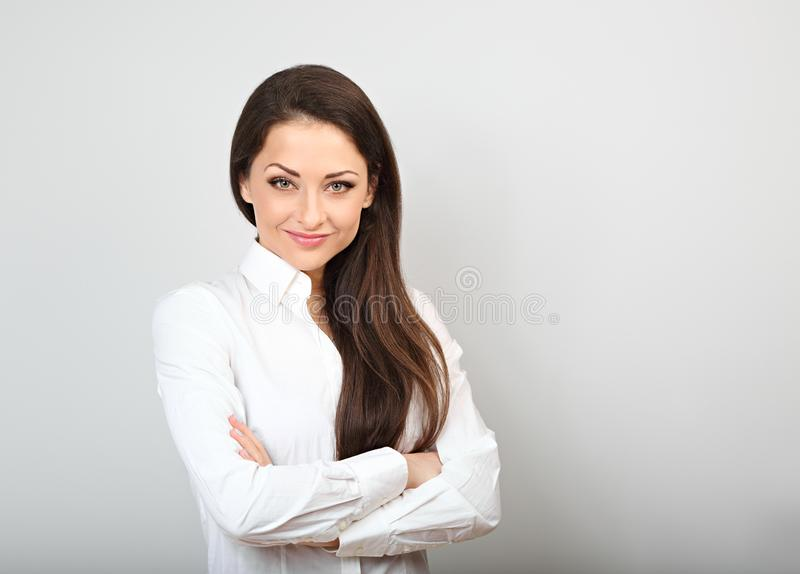Beautiful business calm confident woman in white shirt looking with folded arms on background with empty copy space. Beautiful business calm confident woman in stock photos