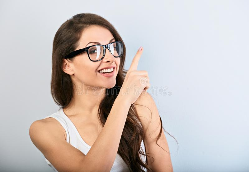 Beautiful business excited casual woman in eyeglasses pointing the finger up with toothy smiling. Closeup portrait royalty free stock photos