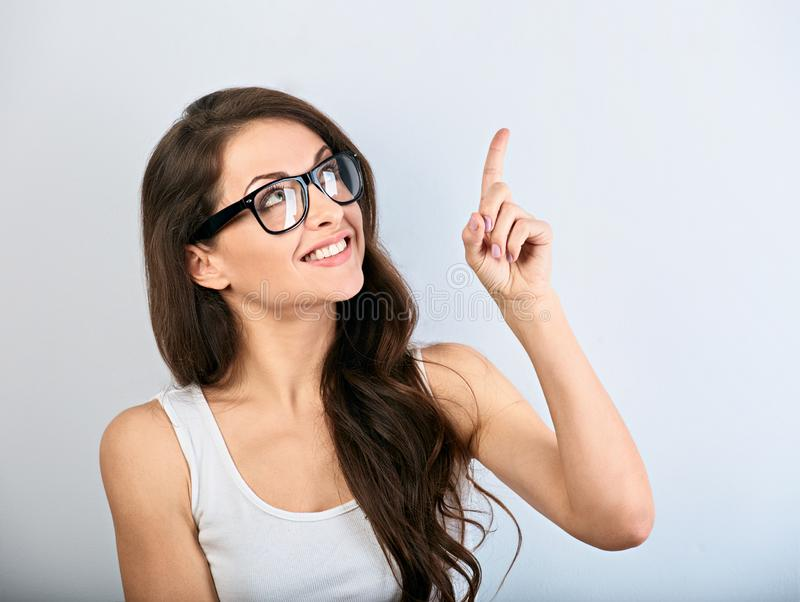 Beautiful business excited casual woman in eyeglasses pointing the finger up with toothy smiling. Closeup portrait stock photos