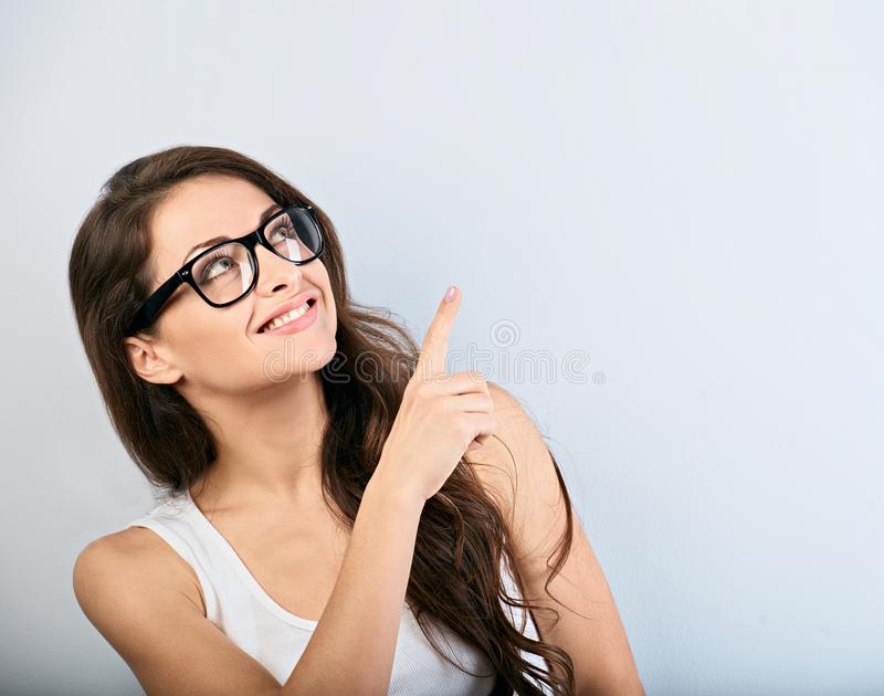 Beautiful business excited casual woman in eyeglasses pointing the finger up with toothy smiling. Closeup portrait stock photography
