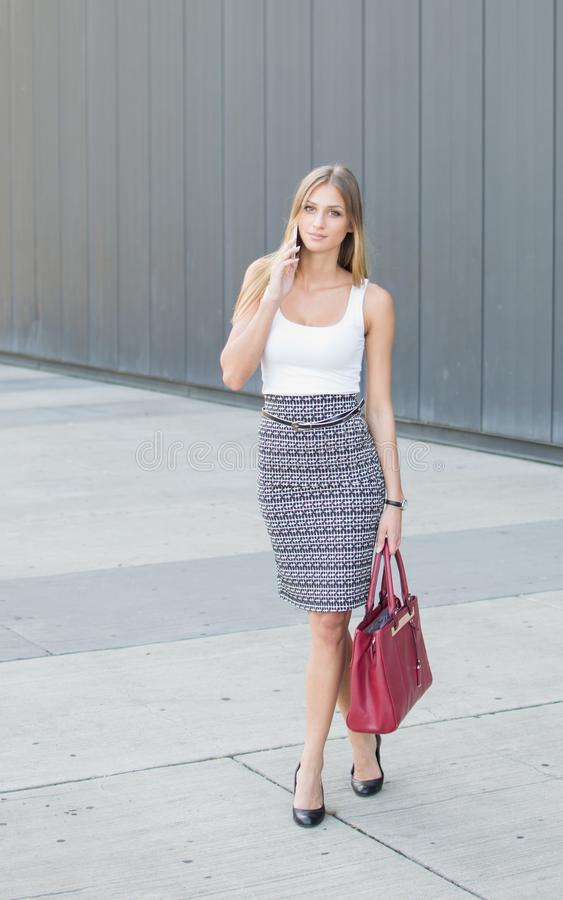 Beautiful business girl talking on the phone with a purse in her hand stock photography