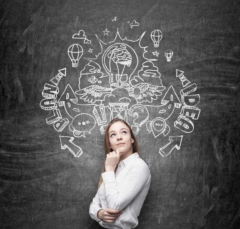 A beautiful business lady is dreaming about an invention of new business ideas for business development. Business plan and idea sk. Etch is drawn on the black stock photography