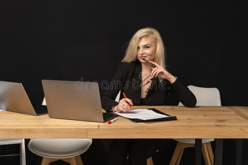 Beautiful business lady is looking at camera and smiling. While working in office with lapto, holding red pen in hand royalty free stock image