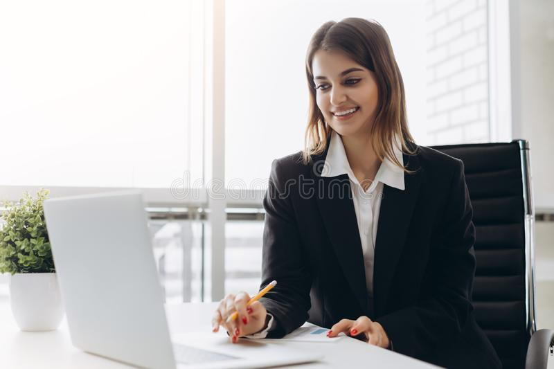 Beautiful business lady is looking at laptop and smiling while working in office. Concentrated on work.  stock image