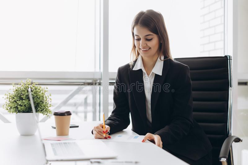 Beautiful business lady is looking at laptop and smiling while working in office. Concentrated on work.  stock photo