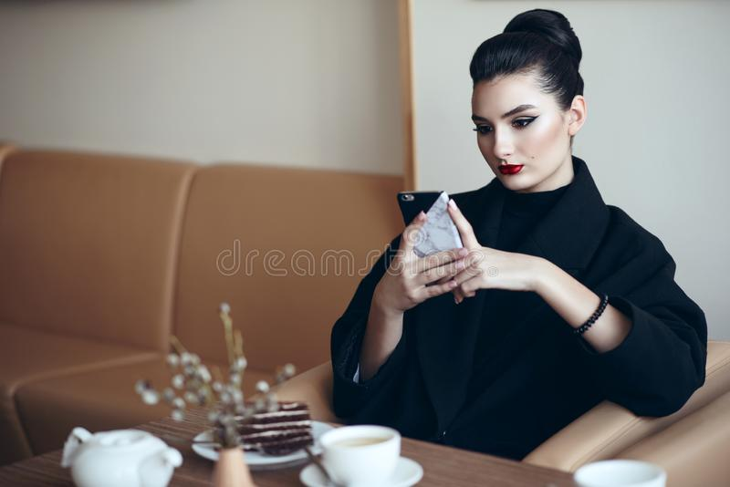 Beautiful business lady with perfect make up sitting in the nice cafe and looking at her phone stock image