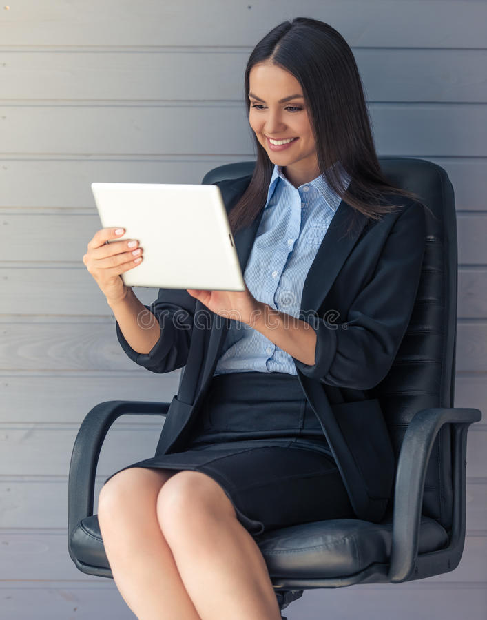 Beautiful business lady. Portrait of beautiful business lady in classic suit using a digital tablet and smiling, sitting on office chair before gray wall royalty free stock photography