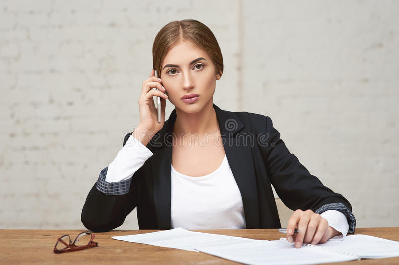 Beautiful business lady talking on the phone. She checks reports royalty free stock photography